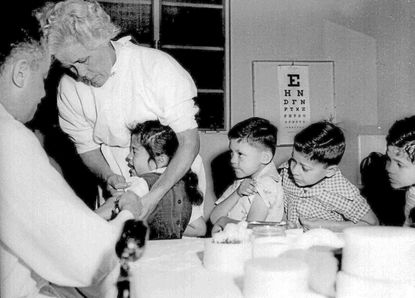 In this April 1955 file photo, first and second-graders at St. Vibiana's school are inoculated against polio with the Salk vaccine in Los Angeles. Tens of millions of today's older Americans lived through the epidemic; polio was ultimately eradicated through vaccination. (AP Photo, File)
