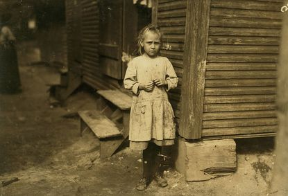 Photographer Lewis Hine, who documented the plight of child laborers in the early 1900s, shot this image of Baltimore-born Marie Kriss, 8 years old, who shucked oysters and picked shrimp at Biloxi Canning Co. in Biloxi, Mississippi, when not tending to a baby. She made 25 cents some days.