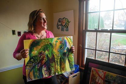 Towson artist Emma Kaufmann poses for a portrait with a painting of elephants she made that was being sold to raise funds for an organization called Elephants For Africa.