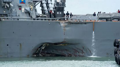 Damage to the portside is visible as the guided-missile destroyer USS John S. McCain steers toward Changi naval base in Singapore following a collision with the merchant vessel Alnic MC in August 2017.
