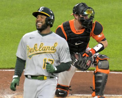Oakland Athletics' Elvis Andrus (17) smiles while crossing the plate past Baltimore Orioles catcher Chance Sisco on a.base hit by Mark Canha during the second inning at Oriole Park at Camden Yards Sat., April 24, 2021. (Karl Merton Ferron/Baltimore Sun Staff)