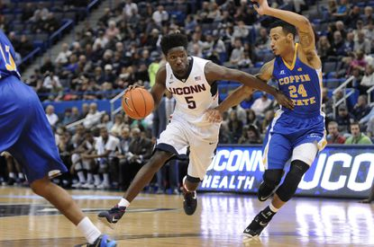 UConn guard/forward Daniel Hamilton drives around Coppin State guard Sterling Smith in the first half.