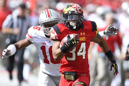 Jacquille Veii runs as Ohio State Buckeyes defensive back Cam Burrows chases at Byrd Stadium.