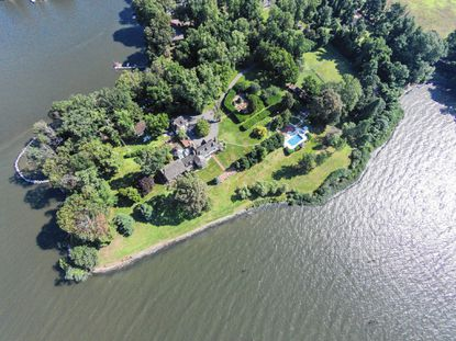 This 9-acre estate features a five-bedroom home, formal gardens, tennis courts, a pool, bath house, greenhouse, a stable and a guest cottage.