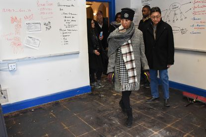 Mayor Catherine Pugh, front, with DPW Chief, Rudy Chow, right, and Baltimore City Schools CEO Sonja Santelises, behind Mayor Pugh, look at a classroom where the flooring needs to be replaced.