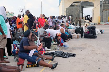 People wait at the Marsh Harbor port in Abaco, Bahamas, to be transported to the capital of Nassau on Sept. 6, 2019.