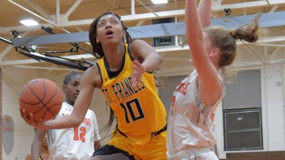 St. Frances forward Angel Reese (10) drives between McDonogh guard Jayla Oden (12) and forward Ava Class to score a basket during a game this past season.