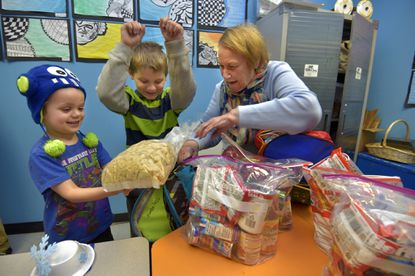 At John Rurah Elementary School, pre-Kindergarten student Jesse McLe and his brother, fourth grader Hunter McLe, receive food from Sandie Nagel, who has organizaed a distribution program.