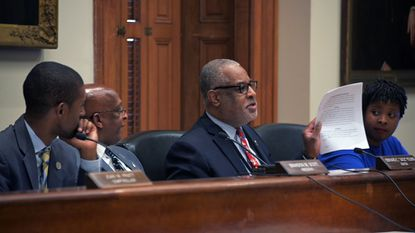 """The Baltimore City Council could once again attempt to limit the mayor's power over city spending by reconfiguring the Board of Estimates. In this Sept. 18, 2019, file photo, Council President Brandon Scott and Mayor Bernard C. """"Jack"""" Young listen to City Solicitor Andre Davis speak during a board meeting."""