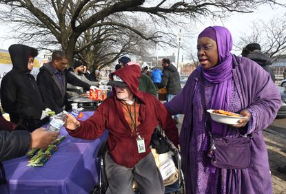 Chili Bowl Sunday founder, Asma Hanif, right, assists Charles Callahan, 67, by holding his bowl of chili as a volunteer offers water, at the annual event held near the Fallsway underpass. The free food event, sponsored by Inge Benevolent Ministries in association with the Muslim Al Nisaa Shelter, has been taking place on Super Bowl Sunday for 25 years, according to Hanif.