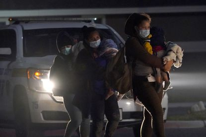 Migrant women carry children at an intake area after turning themselves in upon crossing the U.S.-Mexico border, early Wednesday, March 24, 2021, in Roma, Texas. The Biden administration says that it's working to address the increase in migrants coming to the border. (AP Photo/Julio Cortez)