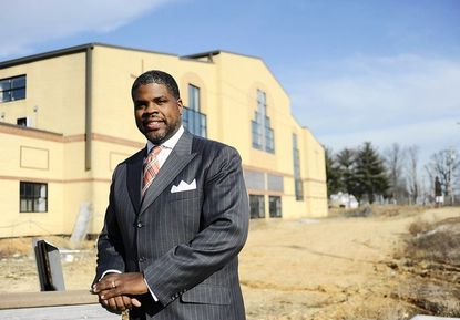 Pastor Tyrone Jones IV stands in front of the First Baptist Church of Guilford, which is now under construction.