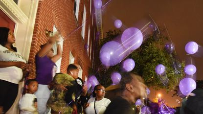 Hazel Wilson, standing second from left, raises her arms to announce the moment to release balloons in memory of her granddaughter, Brailynn Ford, a 5-month-old who died Sunday. Family members, friends and Sandtown neighbors gathered at Mosher Street and Arlingon Avenue.