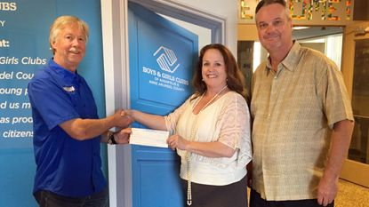 Apple Valley Waste Senior All-Star Classic sponsor Mike Gunther and event director Bill Wagner present a check for $2,500 to Lisa Mondoro, chief executive officer of the Boys and Girls Clubs of Annapolis and Anne Arundel County.