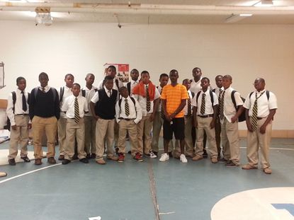 Marvin Matthews (orange shirt) poses with a group of kids he coached.