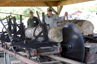 Richard Airing, left, of Taneytown and Mike Rohrer of Smithsburg operate a 1930s Frick Sawmill as it is belt driven by a steam engine during the 59th annual Mason-Dixon Steam and Gas Roundup at the Carroll County Farm Museum in Westminster Friday, Sept. 10, 2021.