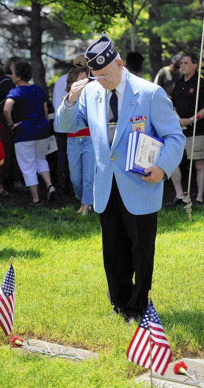 Vincent Krepps of Towson, a veteran of the Korean War, salutes the marker of his twin brother, Richard, at the annual Memorial Day Observance at Dulaney Valley Memorial Gardens. Richard Krepps was declared missing in action shortly before his 20th birthday in 1951.