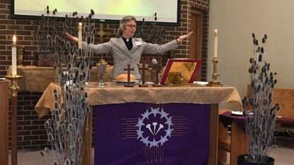 Pastor Anke Deibler leads worship at Calvary Lutheran Church in Woodbine in 2018. On Ash Wednesday the altar has purple but no greenery, weeds and thorns to show the testing of Jesus for 40 days until Easter.