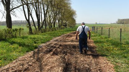 Keith Ohlinger's walks along a mulched road on his farm in Woodbine on Saturday, April 28.