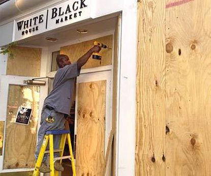 In downtown Annapolis, Terran Hicks Sr. boards up glass at the White House/Black Market clothing store. Storm damage often closes businesses, cutting off worker pay and tax revenue.