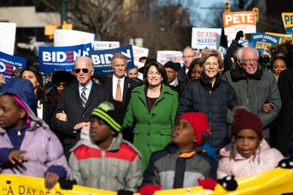 Democratic presidential candidates, former Vice President Joe Biden, left, Sen. Amy Klobuchar (D-Minn.), Sen. Elizabeth Warren (D-Mass.), and Sen. Bernie Sanders (I-Vt.), right, march down Main Street to the King Day at the Dome event on Jan. 20, 2020 in Columbia, S.C.