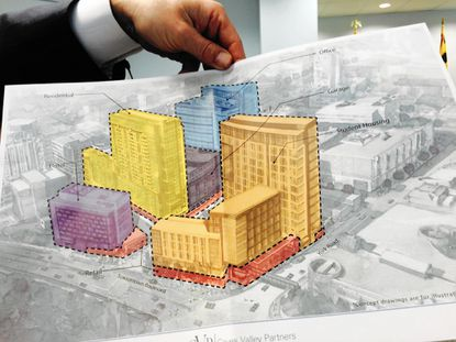 Joshua Glikin, past president of the West Towson Neighborhood Association, hold an artist's rendering of the Towson Row development that was handed to him by an attorney for the developer during a hearing before a Baltimore County administrative law judge on Thursday.