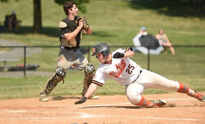 Mt. Airy's Matt Gelhard dives towards home plate, avoiding Sykesville catcher James Andrews, scoring a run in the seventh inning of an American Legion baseball game at Loats Field in Frederick on Friday, June 28.