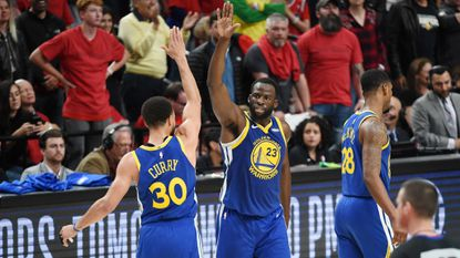 Golden State Warriors' Stephen Curry (30) high fives Draymond Green (23) during the second half against the Portland Trail Blazers in Game 4 of the NBA Western Conference Finals on May 20 in Portland, Ore.