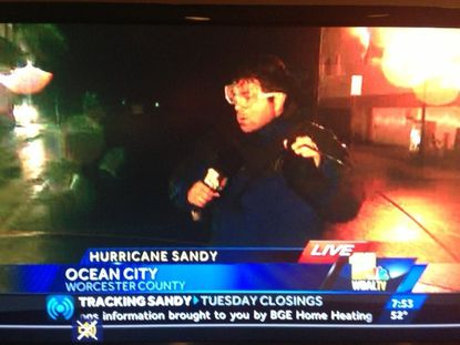WBAL reporter Lowell Melser in the storm Monday night in Ocean City as a piece of metal comes flying toward him
