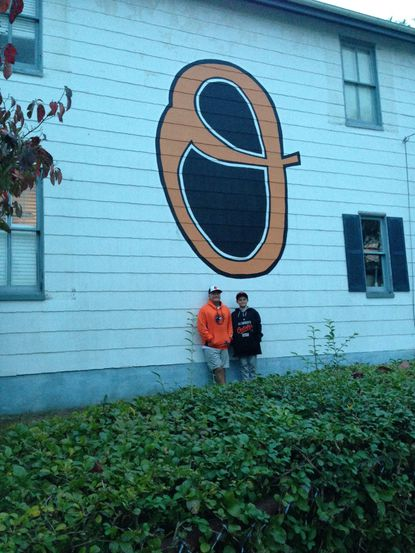 Clif and Caleb Collins stand beneath the giant Orioles logo that is painted on the side of their Sixth Street home in Old Town Laurel.