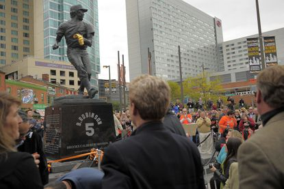 Spectators look at the 9-foot bronze statue honoring Hall of Fame former Orioles third baseman Brooks Robinson. The statue is at the intersection of Russell Street and Washington Boulevard, across from Oriole Park at Camden Yards.