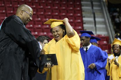 Aniquia Hemphill, right, holds her hat while jumping up and down while principal Dwayne Jones hands her a diploma.