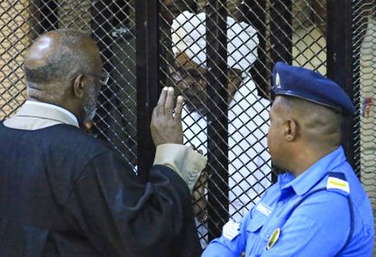 Sudan's deposed president Omar al-Bashir sits in a defendant's cage during his corruption trial at a court in Khartoum on Dec. 14, 2019. The Sudanese court ordered former al-Bashir to be detained for two years in one of several cases against the ousted autocrat. Bashir was toppled by the army in April after months of mass demonstrations.
