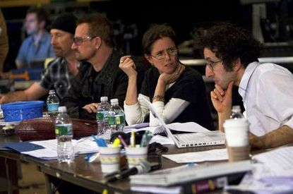 """Glen Berger, right, conferring with Julie Taymor in 2009 during rehearsals for the musical """"Spider-Man: Turn Off the Dark"""" in New York. At left are U2 members the Edge and Bono."""
