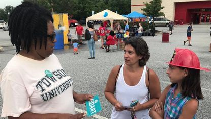 Bonita Buchanan, left, a member of Moms Demand Action for Gun Sense in America, talks with Kelly Burgos, of Belcamp, and her daughter, Haylie, about the group's Be Smart gun safety campaign during National Night Out at the Aberdeen Target on Tuesday.