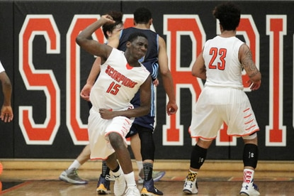 Oakland Mills Mamadou Ndiaye celebrates a basket during overtime against River Hill Wednesday night. Ndiaye finished with 13 points and helped his team to a 61-59 victory.