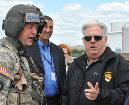 This 2015 photo shows Gov. Larry Hogan, right, arriving at Pier 7 in Canton for a Blackhawk helicopter tour of areas of Baltimore affected by unrest a day earlier. Keiffer Mitchell, a senior advisor to the governor, is in the blue shirt with the ID lanyard. He is now the governor's chief legislative officer.