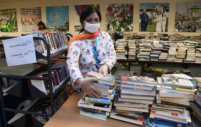 Rizwana Malik, a circulation assistant at the Cockeysville branch of the Baltimore County Public Library, works in the library's quarantine room, where library materials are stored for 72 hours before being released for circulation. (Barbara Haddock Taylor/Baltimore Sun).