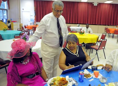 Olivia Rice, of Forest Park, center, signs a book of prayers to end the violence in Ferguson, Mo., being passed around by Rocky Twyman as Vernella Trull, of Randallstown, enjoys her lunch after participating in a prayer vigil at Rising Sun First Baptist Church. Congregation members wore church attire from the 1950's and 1960's that were reminiscent of pre-civil rights days.
