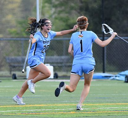 C. Milton Wright's Lydia Cassilly, left, runs to celebrate with teammate Kaitlyn Bajkowski and others after scoring the winning goal in overtime of the game against Fallston at C. Milton Wright Tuesday April 27, 2021.