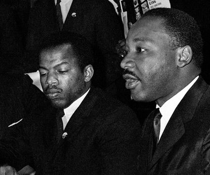 In this April 2, 1965 file photo, Dr. Martin Luther King Jr., second from right, speaks at a news conference next to John Lewis, to his left, chairman of the Student Nonviolent Coordinating Committee, in Baltimore.