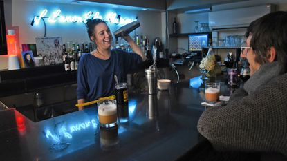 Emily Bach, general manager and bartender at Diskobar, mixes a cocktail and chats with customer Cornel Novac at the music-focused bar in Mount Vernon.