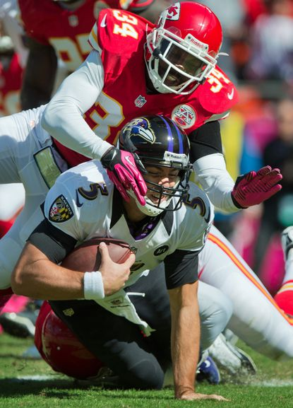 Ravens quarterback Joe Flacco is sacked by Chiefs defensive back Travis Daniels.