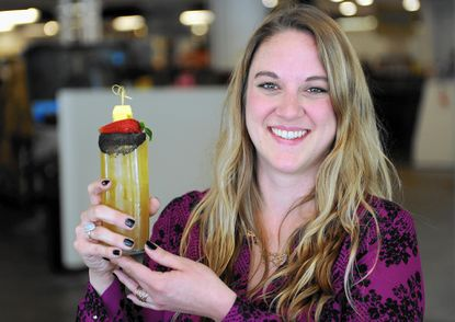 Erin Harper, a bartender at Cultured in the Mt. Vernon Marketplace, holds the cocktail she invented called Up the Stakes.