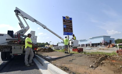 Workers from Shannon-Baum Signs and Graphics install an attractions sign as work continues on the Westminster Station Shopping plaza along Md. 140 Friday, August 28, 2020. A CVS Pharmacy and a 16,400-square-foot shopping plaza are proposed for project along a stretch of Md. 140 across from the TownMall of Westminster.