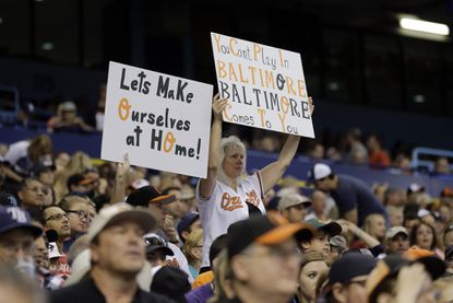 Baltimore Orioles fans hold up signs during the first inning against the Tampa Bay Rays Saturday in St. Petersburg, Fla. The game was moved from Baltimore because of the unrest, and it proved to be more exciting than the big boxing match later in the night.