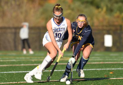 Liberty's Meghan Huey, left, tries to maneuver around the defense of Kent County's Kate Erivn during a 1A state quarterfinal field hockey game at Western Regional Park on Friday, November 1.