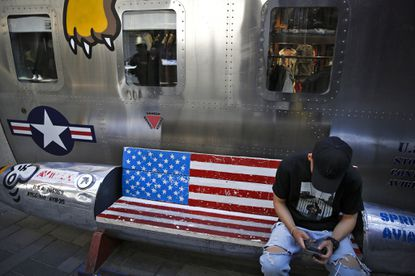A man browses his smartphone on a bench with a decorated with U.S. flag outside a fashion boutique selling U.S. brand clothing at the capital city's popular shopping mall in Beijing, Monday, May 13, 2019.