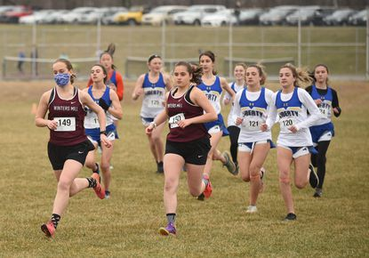 Winters Mill teammates and sisters Kathryn, left, and Makenzie Hopkins lead the field at the start of the girls race during a cross country meet at Liberty High School on Wednesday, March 17, 2021.