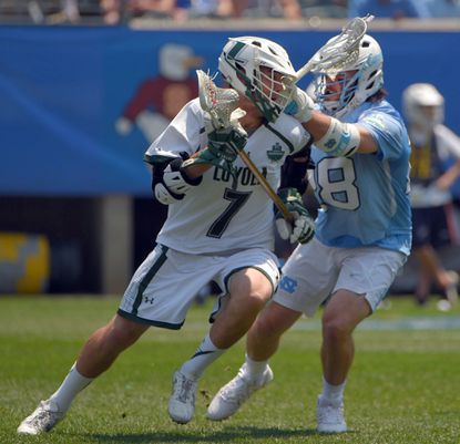 Loyola Greyhounds attack Pat Spencer (7) attempts to move the ball while North Carolina Tar Heels midfielder Tate Jozokos defends during the 2016 NCAA men's lacrosse Division I championship semifinals.